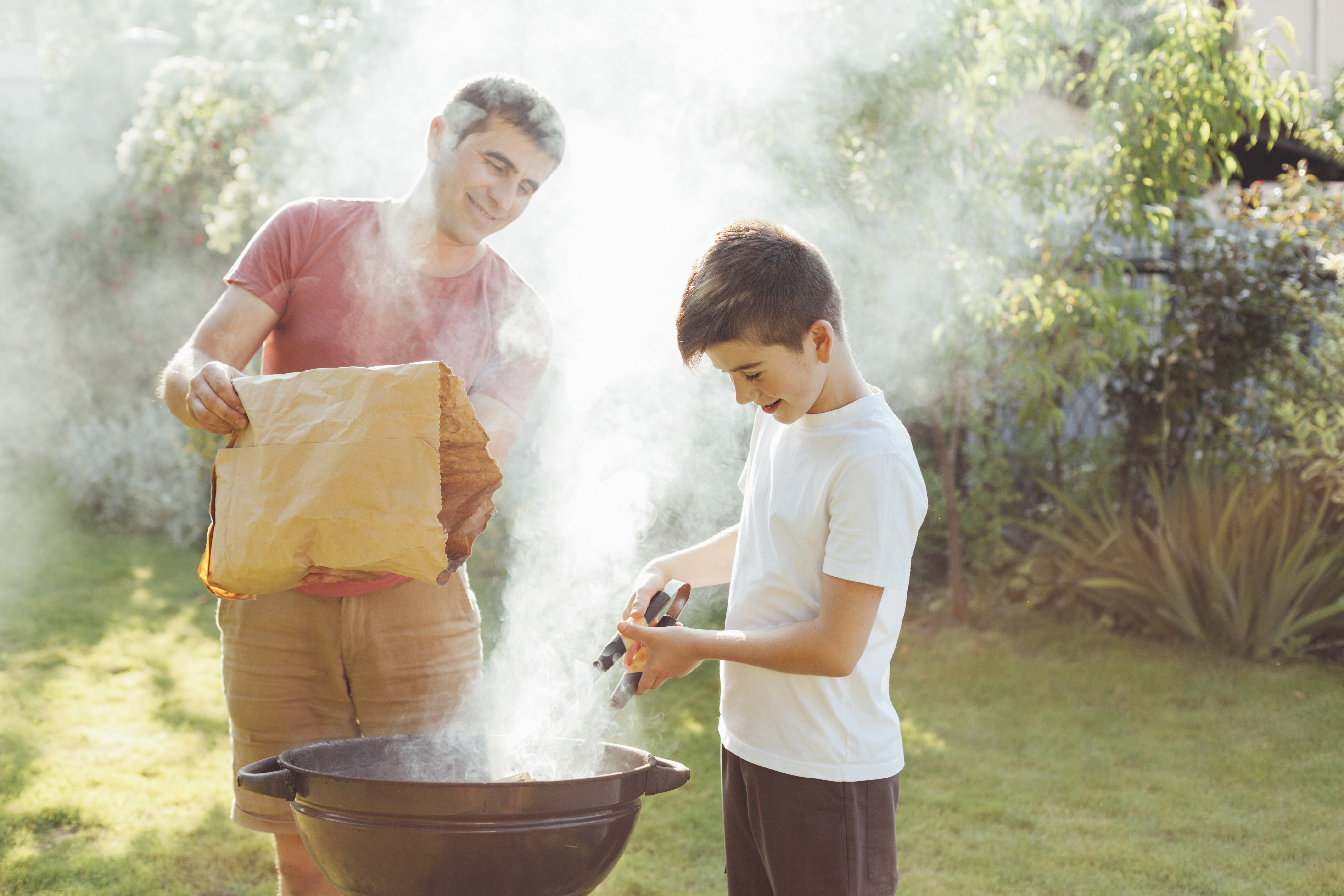 A father and his son having good time barbequing. Plenty of smoke comes are coming out of their oven.
